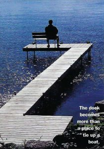 photo of a person sitting on a bench on a dock